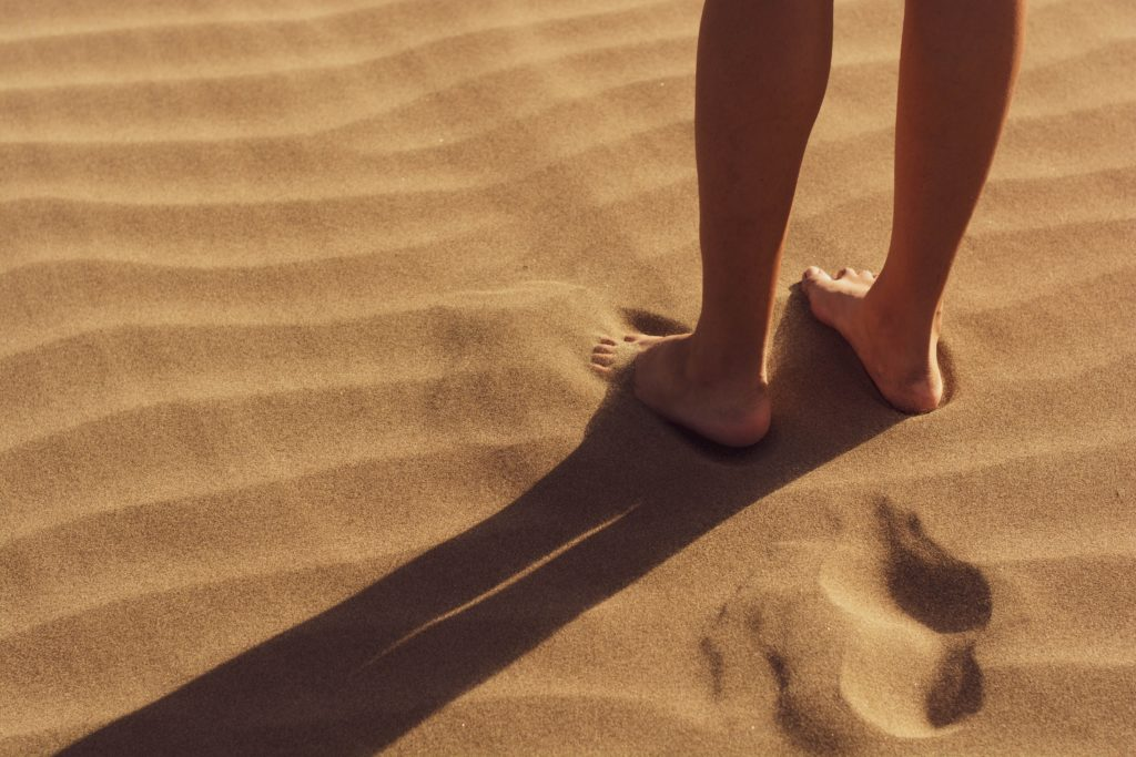 standing barefoot on the sand
